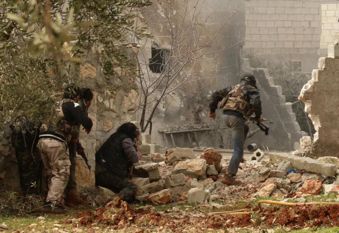 A rebel fighter carries his weapon as he runs while others take positions in Ratian village, north of Aleppo