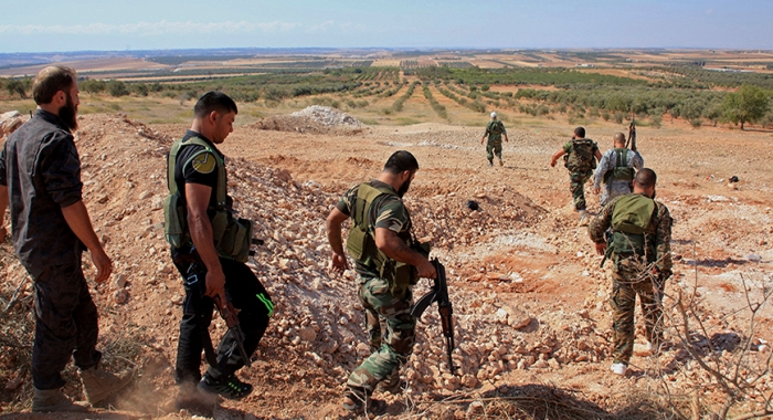 Forces loyal to Syria's President Assad carry their weapons as they walk in the village and hill of Al-Samsam