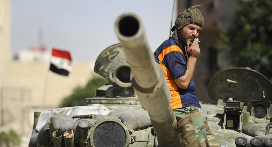A soldier loyal to Syria's President Bashar Al-Assad smokes while resting on a tank in Adra al-Omalia, after taking control of the area from rebel fighters
