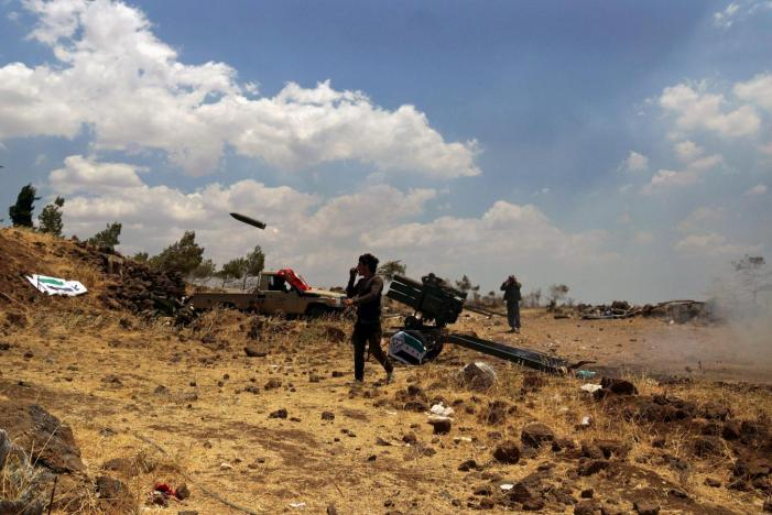 Free Syrian Army fighters fire rockets towards forces loyal to Assad in the northern countryside of Quneitra, Syria