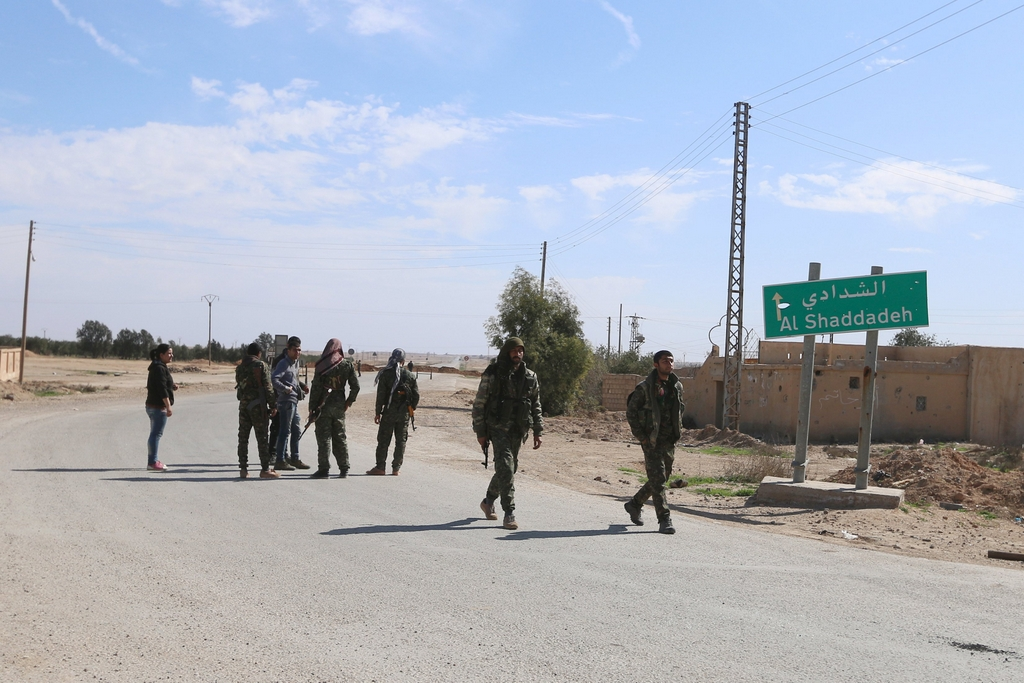 Syria Democratic Forces walk near a sign on the outskirts of al-Shadadi town, Hasaka countryside