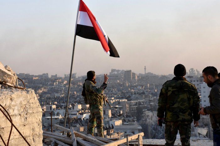 A Syrian government soldier gestures under the Syrian national flag near a general view of eastern Aleppo