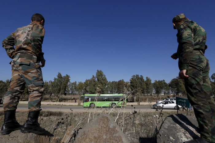 Syrian Army forces look on as buses leave district of Waer during a truce between the government and rebels, in Homs