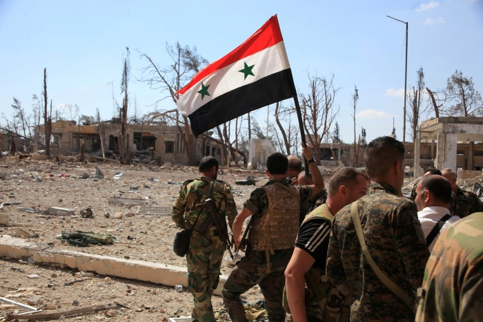 A file photo shows forces loyal to Syria's President Bashar al-Assad walking at a military complex as one of them holds up a Syrian national flag, after they recaptured areas in southwestern Aleppo on Sunday that rebels had seized last month