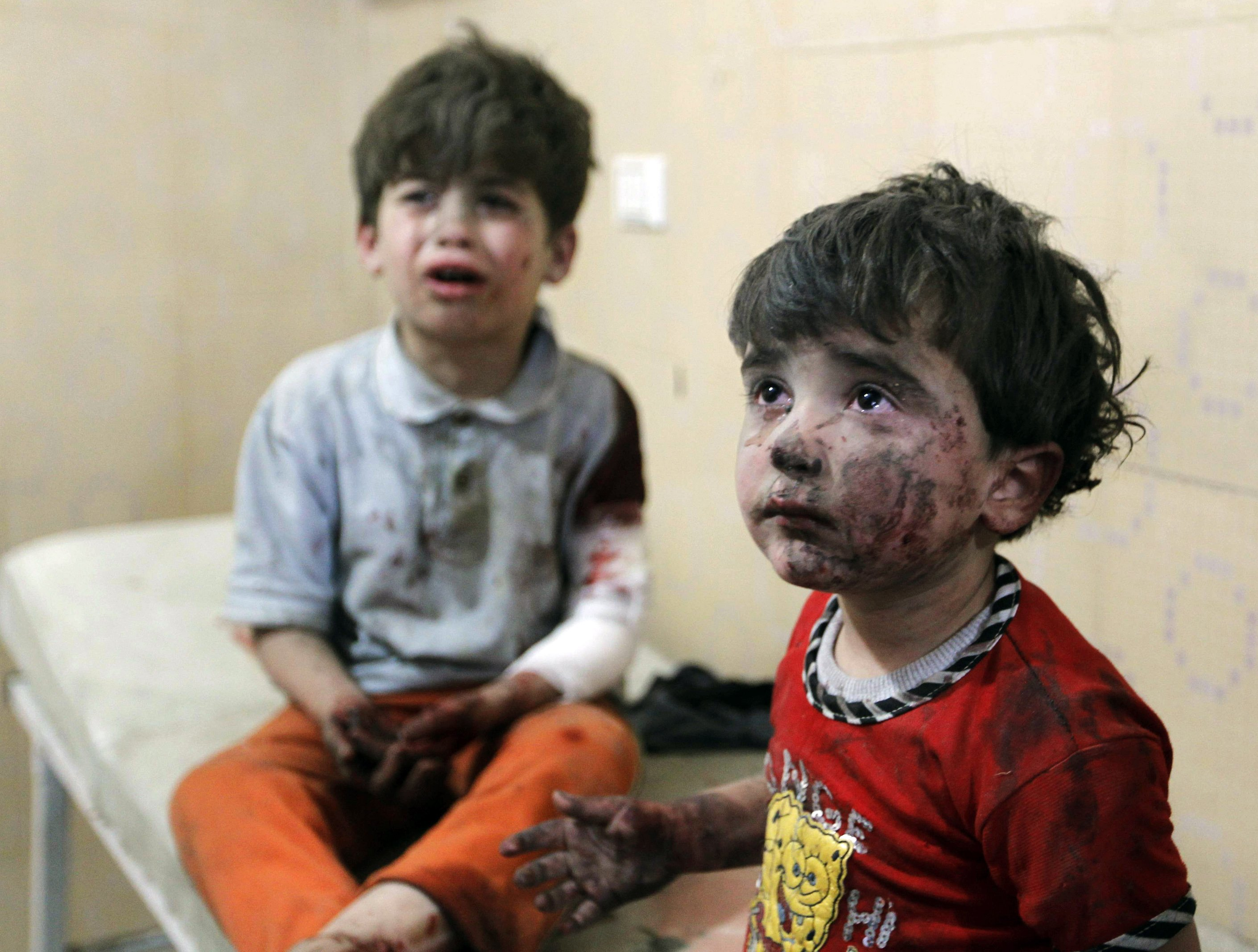 Injured children cry after, according to activists, two barrel bombs were thrown by forces loyal to Syria's president Bashar Al-Assad in Aleppo