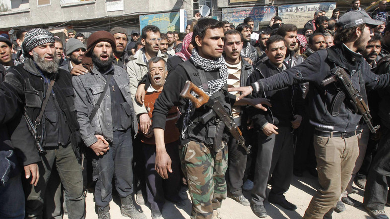 Members of Syria's armed opposition and soldiers loyal to Syria's President Bashar al-Assad are seen in Babila town, southeast Damascus after a local ceasefire agreement was reached