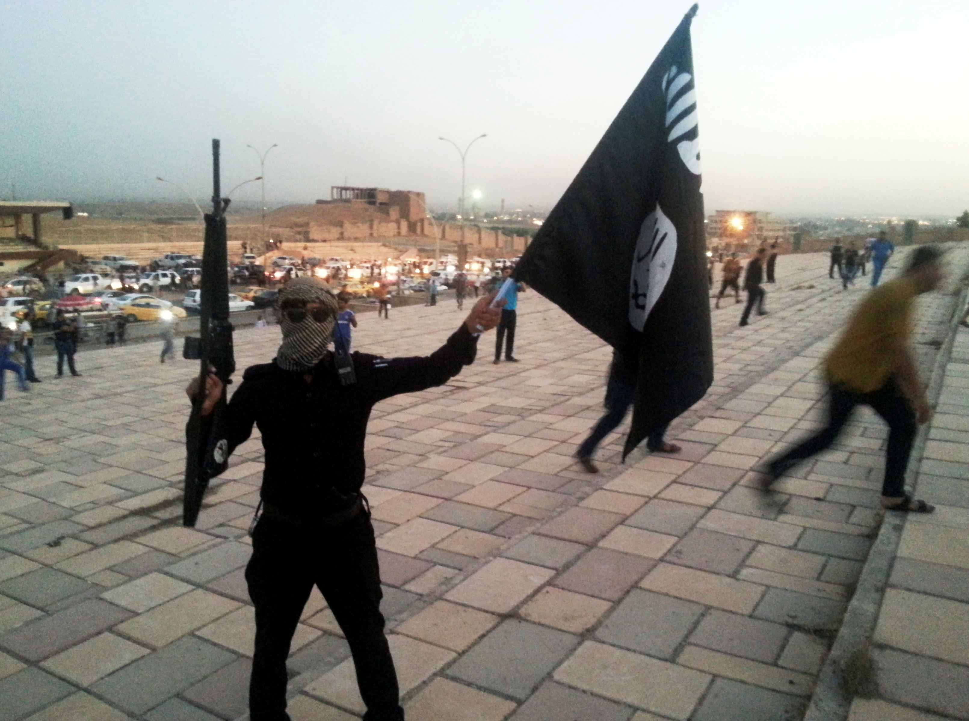 ISIL fighter holds a flag and a weapon on a street in Mosul