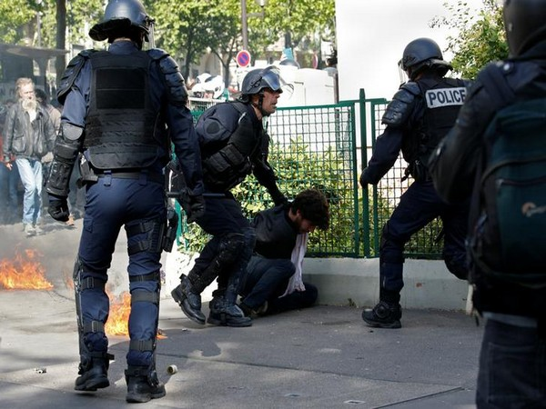 French police apprehend a demonstrator during clashes at the traditional May Day labour union march in Paris