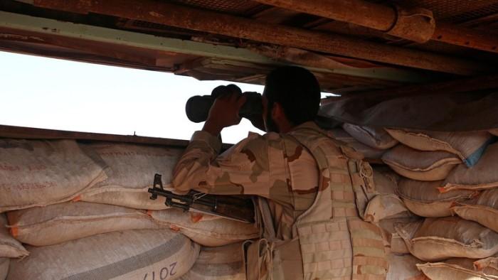 A Free Syrian Army fighter looks through binoculars in rebel-held Al-Yadudah village, in Deraa Governorate