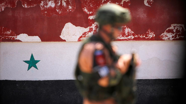 A Russian soldier stands guard near a Syrian national flag drawn on the wall as rebel fighters and their families evacuate the besieged Waer district in the central Syrian city of Homs