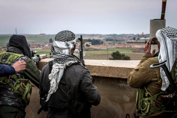 Fighters of the Kurdish People's Protection Units (YPG) carry their weapons and use a pair of binoculars in the outskirts of Tal Tamr town as they monitor the movements of Islamic State fighters who recently captured several villages