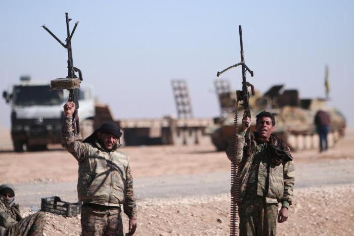 FILE PHOTO: Syrian Democratic Forces (SDF) fighters hold up their weapons in the north of Raqqa city