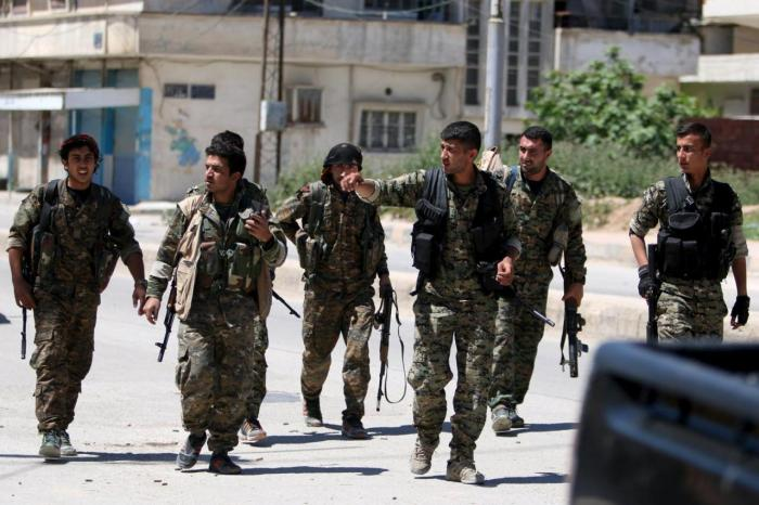 Kurdish fighters from the People's Protection Units (YPG) walk along a street in the southeast of Qamishli city