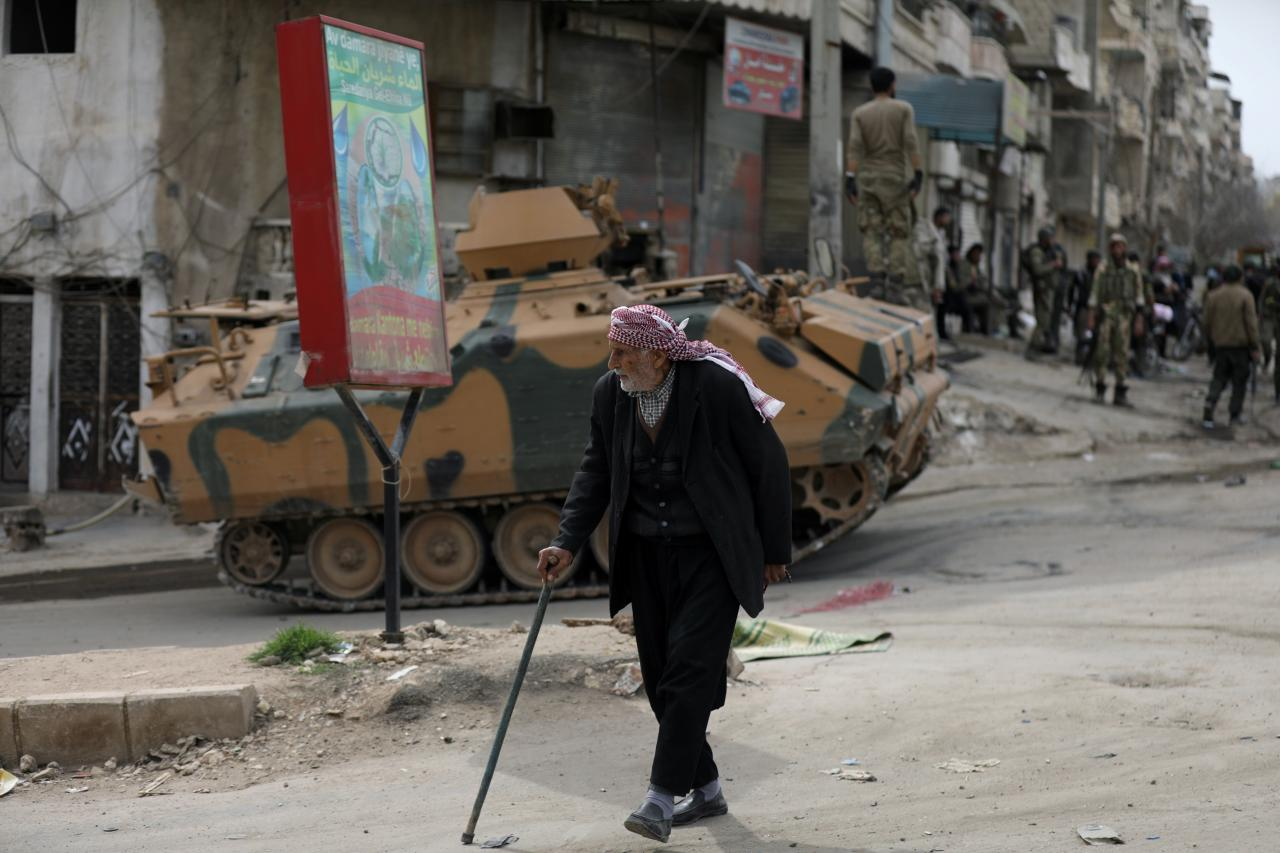 A Kurdish elderly man walks with a cane in Afrin